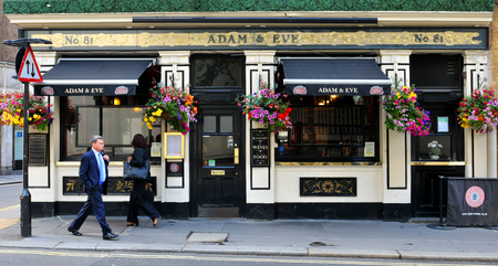 british food: LONDON, UK. JULY 9, 2014: Pedestrians pass by the entrance to traditional British pub in central London Editorial