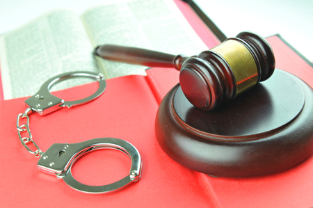 martial law: Law concept with gavel and handcuffs against red book Stock Photo
