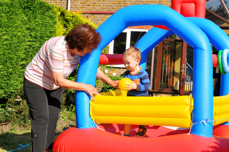 grandmother and children: Grandmother and child play in a colorful bouncing castle