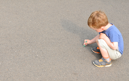 sidewalk: Portrait of a child writing with chalk on concrete