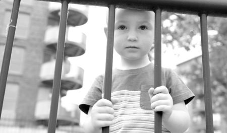 restrictive: Depressed child behind the bars