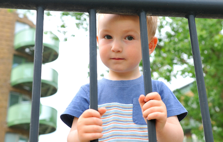orphan: Portrait of a sad child behind the bars