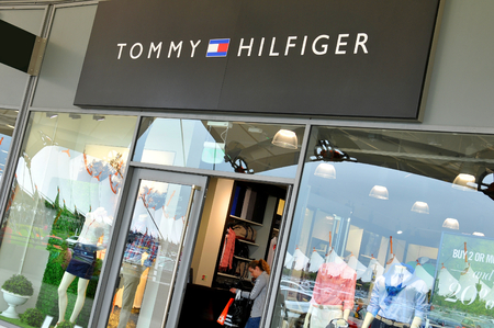 tommy: London, UK - June 14, 2015: People pass by the Tommy Hilfiger shop. Tommy Hilfiger is a famous worldwide American fashion