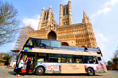 lincoln: Lincoln, UK - April 9, 2015: Tour bus stops in front of the Lincoln Cathedral, major landmark and third largest cathedral in UK