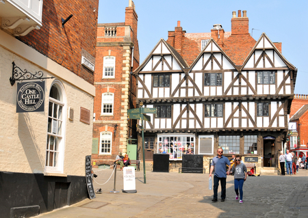 midlands: Lincoln, UK - April 9, 2015: Tourists walk along the cobbled streets of Lincoln, a cathedral city and the county town of Lincoln