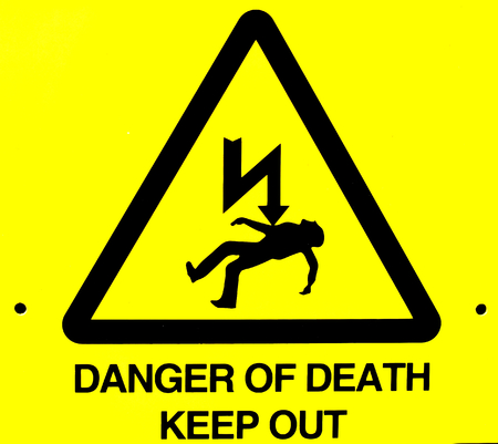 warns: Close up of danger of death yellow warning sign Stock Photo