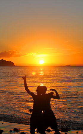winning location: Two boys cheer happily at sunset Stock Photo