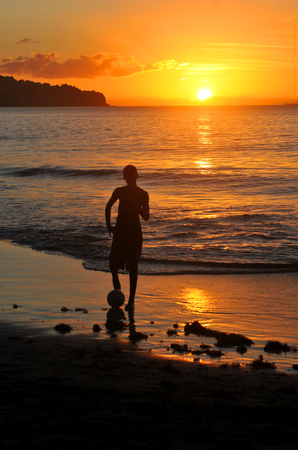 Boy plays football on the beach at sunset photo