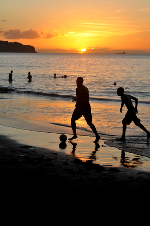 Boys play football on the beach at sunset photo