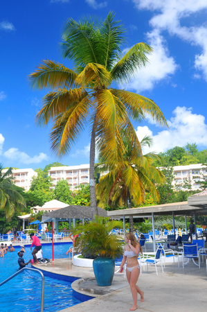 saint lucia: SAINT LUCIA, CARIBBEAN - DECEMBER 10, 2014:  Tourists relax by the pool in exotic resort in Saint Lucia, Caribbean