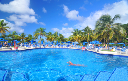 st lucia: SAINT LUCIA, CARIBBEAN - DECEMBER 10, 2014:  Tourists relax by the pool in exotic resort in Saint Lucia, Caribbean