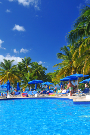 caribbean beach: SAINT LUCIA, CARIBBEAN - DECEMBER 10, 2014:  Tourists relax by the pool in exotic resort in Saint Lucia, Caribbean