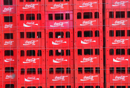 illustrative editorial: Bucharest, Romania - June 24, 2015: Stacks of Coca Cola boxes advertised on the street of Bucharest. Coca-Cola is a popular carbonated soft drink sold in stores, restaurants, and vending machines throughout the world illustrative editorial.