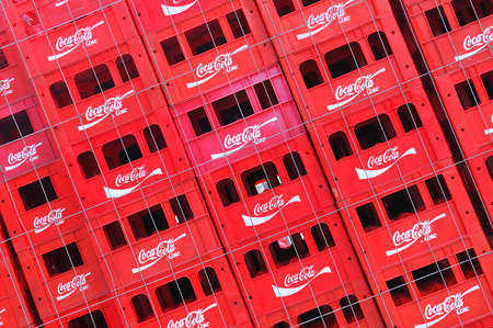 advertised: Bucharest, Romania - June 24, 2015: Stacks of Coca Cola boxes advertised on the street of Bucharest. Coca-Cola is a popular carbonated soft drink sold in stores, restaurants, and vending machines throughout the world illustrative editorial.