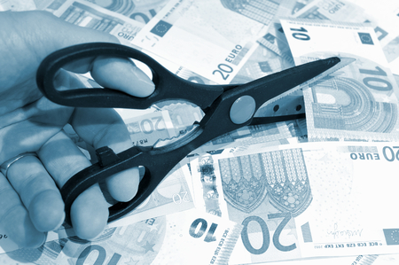 budget restrictions: Budget cut concept with scissors and euros