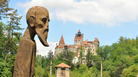 Ancient statue overlooks Bran Castle also known as Draculas Castle Editorial