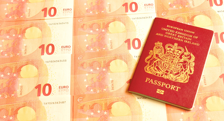 naturalization: UK in euro zone concept with British passport and euro banknotes Stock Photo