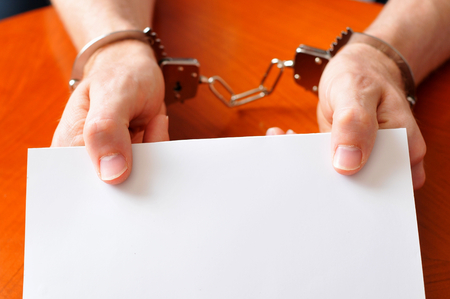 convict: Convict with handcuffs shows blank card Stock Photo