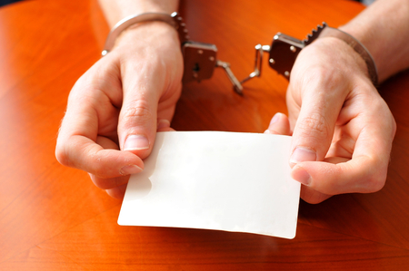 lawful: Convict with handcuffs shows blank card Stock Photo
