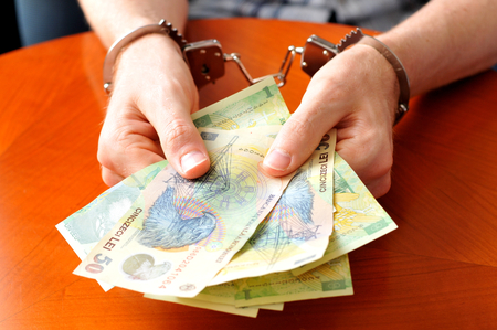 Convict with handcuffs shows pile of money