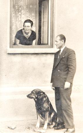 Old photo depicting senior couple with dog