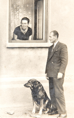 Old photo depicting senior couple with dog