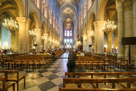church: París, Francia - 7 de julio de 2015: Los turistas visitan el interior de Notre-Dame, punto de referencia en París, Francia