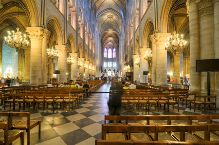 people in church: Paris, France - July 7, 2015: Tourists visit the interior of Notre-Dame cathedral, major landmark in Paris, France