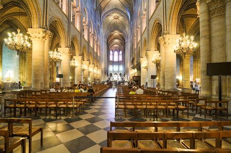 Paris, France - July 7, 2015: Tourists visit the interior of Notre-Dame cathedral, major landmark in Paris, France