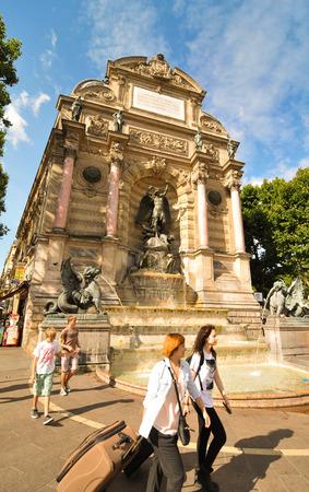Paris, France - July 7, 2015: Tourists pass by the Fountain Saint Michel in Paris , France