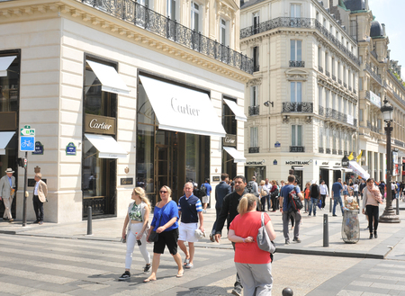 champs elysees: Paris, France - July 9, 2015: People pass by the famous Cartier fashion store on Champs Elysees in central Paris, France Editorial