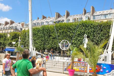 bungee jumping: París, Francia - el 9 de julio de, 2015: la gente se divierte en puenting inversa en parque de atracciones por Museo del Louvre en Jardín de las Tullerías, París Editorial