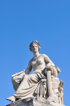 empress: Architectural detail of statue depicting woman pouring water against blue sky