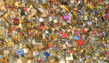 fastened: Paris, France - July 9, 2015: Detail of love locks symbolically fastened to the railings of the Ponts des Arts in Paris. Tying a love lock on to the Pont des Arts before throwing the key into the River Seine beneath has become a tourist tradition in r