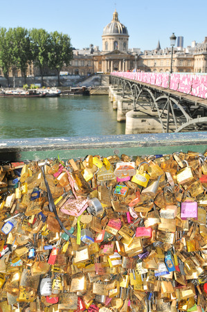 symbolically: Paris, France - July 9, 2015: Detail of love locks symbolically fastened to the railings of the Ponts des Arts in Paris. Tying a love lock on to the Pont des Arts before throwing the key into the River Seine beneath has become a tourist tradition in r