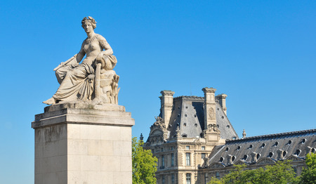 architectural heritage of the world: Paris, France - July 9, 2015: Architectural detail of statue depicting woman pouring water with Louvre Museum in the background
