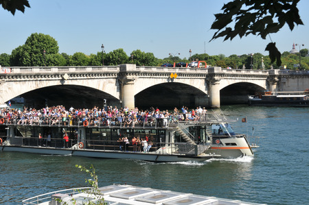 embark: Paris, France - July 9, 2015: Tourists embark on cruise boat on river Seine by Orsay Museum in Paris, France