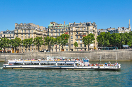 embark: Paris, France - July 9, 2015: Tourists embark on Bateaux Mouches cruise boat by Orsay Museum in Paris, France. There are several boat tours across the river Seine showing tourists the major local landmarks in Paris.