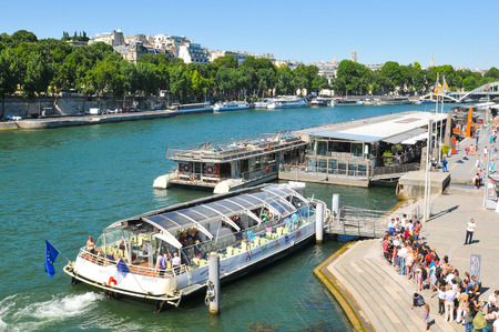 embark: Paris, France - July 10, 2015: Tourists embark on bateau bus, a boat service along the River Seine in the Paris region. Editorial