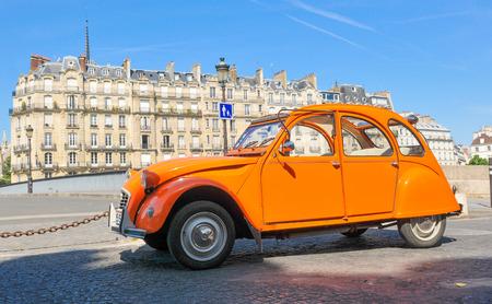 Parijs, Frankrijk - 10 juli 2015: Vintage oranje auto is geparkeerd in de wijk Marais in Parijs