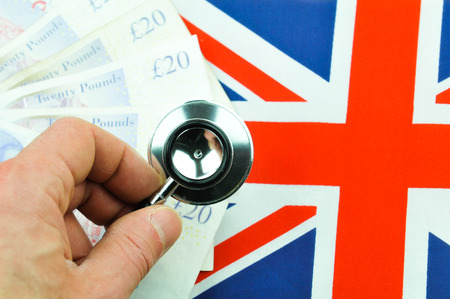 britain: British pound concept  with currency, stethoscope and UK flag Stock Photo