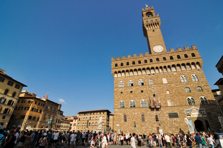 Florence, Italy - June 24, 2016: Tourists visit Palazzo Vecchio, an iconic building located in Piazza della Signoria in Florence, Italy