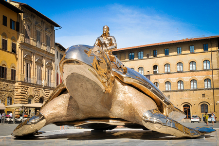 """Florence, Italy - June 25, 2016: Modern sculpture entitled """"Searching for Utopia"""" is displayed in Piazza della Signoria in Forence, Italy as part of """"Spiritual Guards"""", an exhibit by Belgian artist Jan Fabre."""