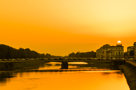 Old buildings overlook the Arno river in Florence, Italy at sunset Stock Photo