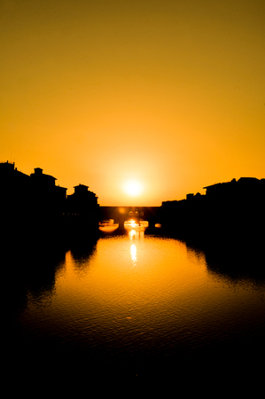 Old bridge over the Arno river at sunset in Florence, Italy