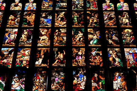 stained glass panel: Milan, Italy - June 27, 2016: Close-up of colorful stained glass depicting religious scenes inside the Cathedral (Duomo) in Milan, Italy Editorial
