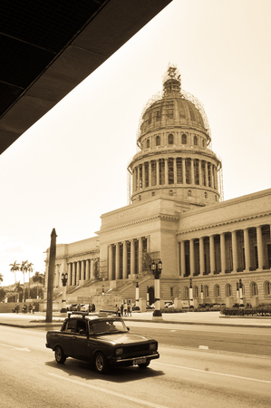capitolio: Havana, Cuba - December 19, 2016: Retro cars pass the Capitol building (El Capitolio) in the heart of Habana Vieja (Old Havana) in Cuba Editorial