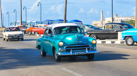 Havana, Cuba - December 19, 2016: Tourists sightseeing in retro cars on Malecon, major avenue in Havana, Cuba Editorial