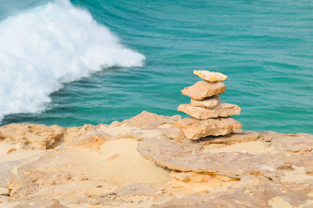 Meditation, relaxation, or life balance concept with pile of rocks against marine landscape