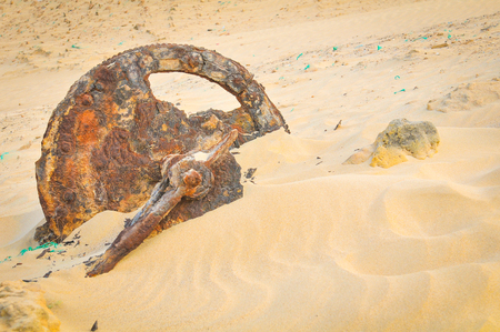 View of desert landscape with dunes and rusty wheel